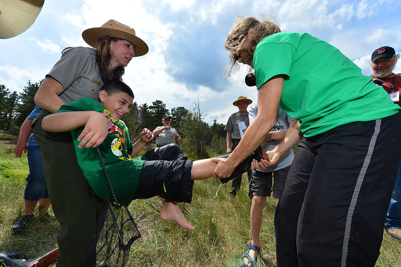 Walt Hester | Trail-Gazette<br /> Rocky's information officer Kyle Patterson helps remove water-logged boots in Upper Beaver Meadows on Friday. Park employees have to be flexible as they can be called upon to do a wide variety of tasks.