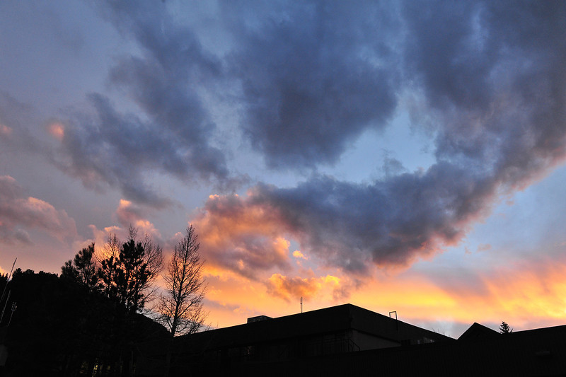 Clouds catch the colorful rays of the fading day above Estes Park on Saturday. A mix of sun and clouds is expected throughout the week in Estes Park.