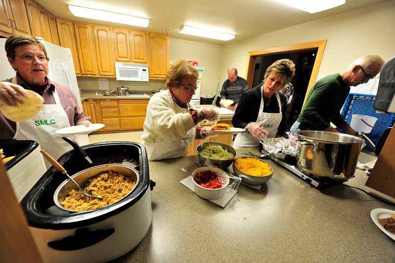 Walt Hester | Trail-Gazette<br /> Comminuty Corner Café volunteers serve up a taco dinner at Sheperd of the Mountains Lutheran Church on Friday. The program, designed to promote a sense community, has extended from December through the end of April.