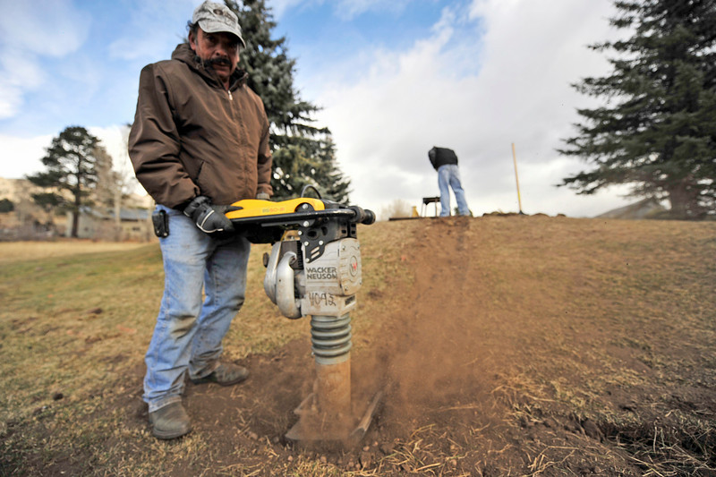 Walt Hester | Trail Gazette<br /> Nicolas Ruvalca, left, and Pedro Luna replace dirt after helping install a new sprinkler system at the Lake Estes Nine-hole golf course on Monday.