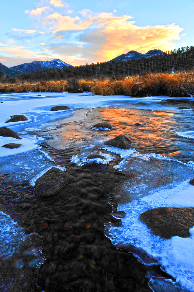 Walt Hester | Trail-Gazette<br /> Sunset-colored clouds reflect on the icy Big Thompson river as it spilles out of Moraine Park on Monday. Warmer weather is expected by the end of the week in Estes Park.