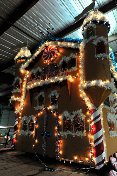 "Walt Hester | Trail-Gazette<br /> A gingerbread castle glows in Barn ""W"" at the fairgrounds on Tuesday. The last lights, tinsle and bobbles are being placed on the foats ahead of the November 26 Catch the Glow Parade."