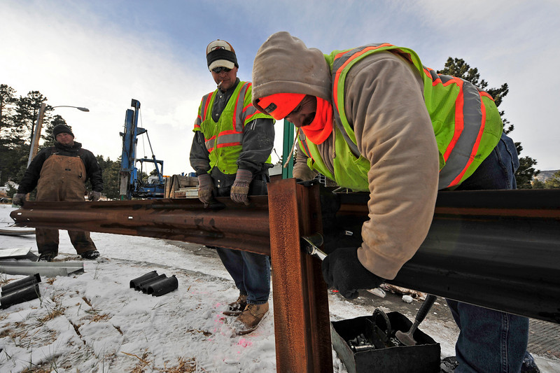 Walt Hester | Trail-Gazette<br /> Martin Fuentes, far left, Ben Hill and Juan Gonzalez, with wrench, assemble new guard rails along Moccasin Drive on Wednesday. The Guard rails should help keep drivers on the road and out of the ditch on the north side of the road near the hospital.