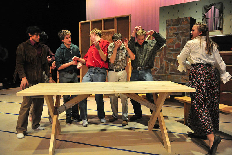 The brothers dive out of the way as Milly Bradon, plyed by Stephanie Soliday loses her cool in the Estes Park High School production of Seven Brides for Seven Brothers. Theproduction plays at the high school on Friday and Saturday at 7 p.m.