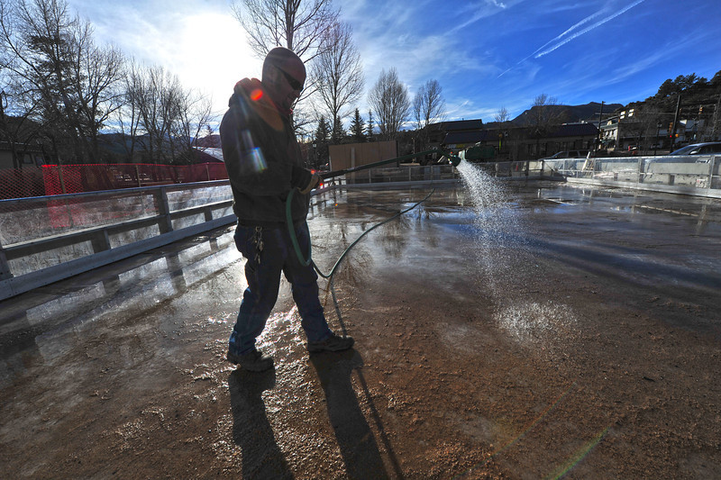 Charles Burnham puts water down on the temperary skating rink on Riverside Drive and Elkhorn on Wednesday. The rink should be ready for next week's busy holiday.