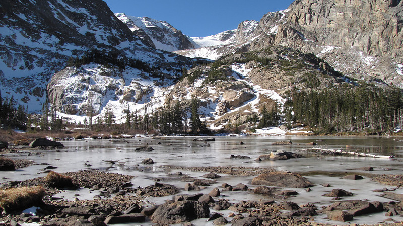 A somewhat frozen Lake Helene sits high in the Colorado Rockies.