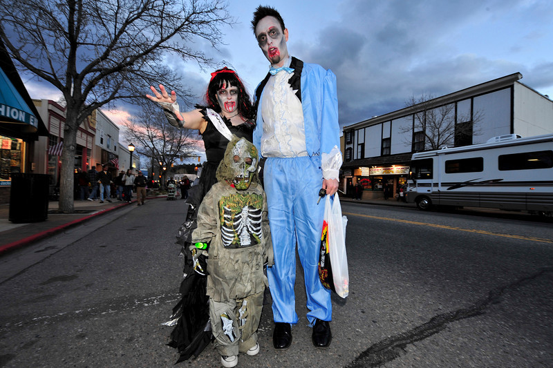 Walt Hester | Trail-Gazette<br /> Shell, left, Miles, 5, and Shawn Hanselman shamble down Elkhorn Avenue in search of brai . . . no wait, candy!