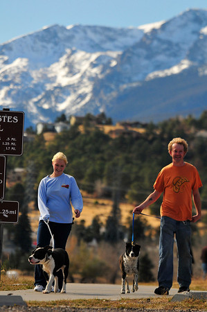 Walt Hester | Trail-Gazette<br /> Whitney Mankin and Aaron Stolz walk dogs Shady and Lila on the Lake Estes Trail on Tuesday. Nice weather is expect to continue through the weekend.