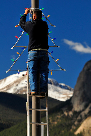 Walt Hester | Trail-Gazette<br /> Orlando Luna hangs holiday decorations along Big Thompson Avenue on Tuesday. While snow covers the high peaks, very non-holiday weather continues for the rest of the weekend.