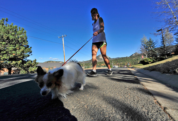 Walt Hester | Trail-Gazette<br /> Linda McQuinn of Estes Park jogs up Brodie Avenue with her tiny running partner on Wednesday. Temperatures should remain in the high 50s andlow 60s for the weekend.