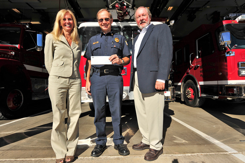 Photo by Walt Hester<br /> Fire Chief Scott Dorman smiles on Tuesday while holding a check from Shelly Doggett, left, and Gary Grenzke representing Insurence Associates of Estes Park and Travelers Insurance. The money, $1,500, will be used to purchase a mobile gel fire supression system.