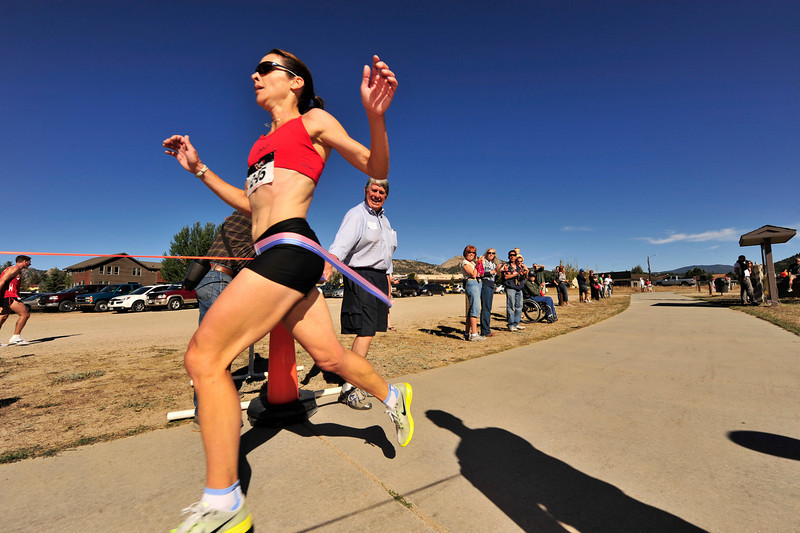 Photo by Walt Hester<br /> Tanya Poel of Boulder breaks the tape as the women's winner of the Running of the Bulls at the Lake Estes Marina on Saturday. Poel finished in 22:48, third overall behind the men's top two.