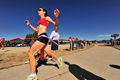 Photo by Walt Hester Tanya Poel of Boulder breaks the tape as the women's winner of the Running of the Bulls at the Lake Estes Marina on Saturday. Poel finished in 22:48, third overall behind the men's top two.