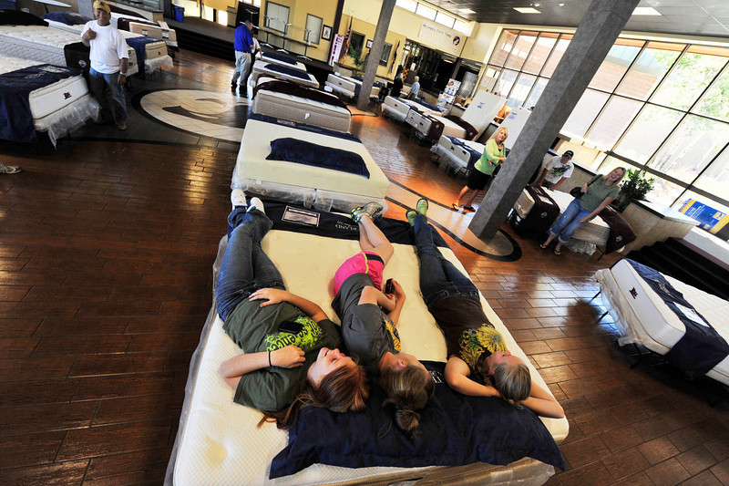 Photo by Walt Hester<br /> Ali Scheil, 14, of Estes Park lies between friends Johna Westfahl, 16, left, and Ali Peters at the mattress sale fund raiser for Estes Park sports teams on Sunday.