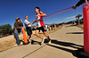 Photo by Walt Hester<br /> Lonnie Cruz of Denver sprints across the finish line well ahead of the next finisher at Saturday's Running of the Bulls. Cruz was the winner of last spring's Fit Family 5-Mile race, as well.
