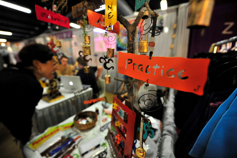 """Photo by Walt Hester<br /> Metal ornaments hang above a jewelry display at the conference's """"Market Place"""" on Saturday. Like any persuite or hobby, yoga has a whole industry creating gifts, books, clothing and even vacations for those who practice."""
