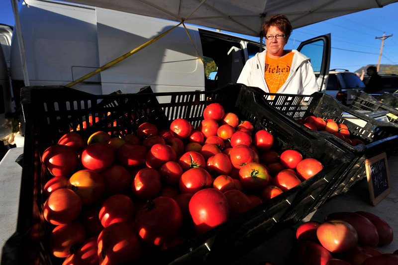 Photo by Walt Hester<br /> Carrie Heaton of Flowers for Three conjers up the season's last red, ripe tomatoes for Thursday's final farmers market. The Estes Valley Farmers' Market will return in June.