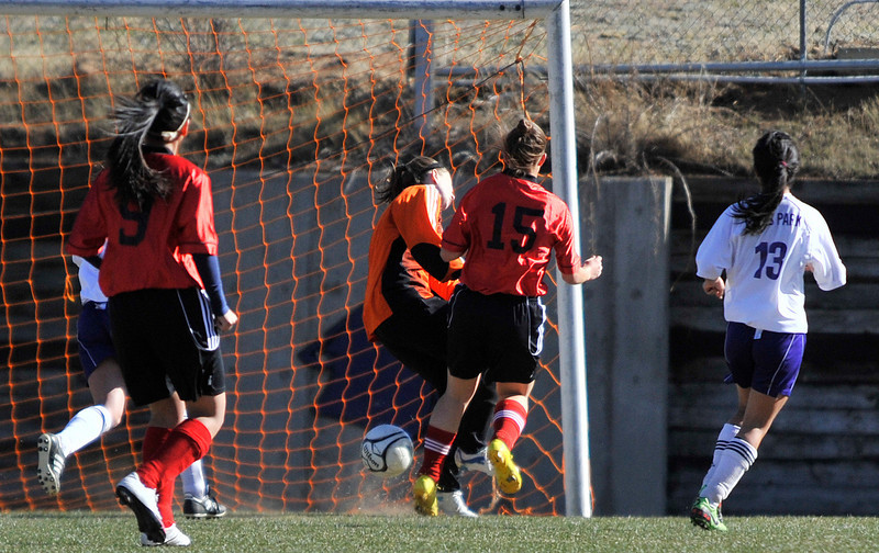 Walt Hester | Trail Gazette<br /> Sophomore goalkeeper Rachel Hughes, in orange, collides with DSST's Traci Morgan during the first half of the Ladycats' tilt with the Denver school. Rachel ultimately made the save, but left the game at the half due to an injury from the collision.