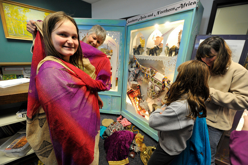 Walt Hester | Trail Gazette<br /> Mary Ringgenberg, 11, tries on a traditional silk wrap, or sari,  from south Asia during the Bridges of Understanding. Each of the display cases has drawers with things in them for students to explore, like clothing, toys and instruments.