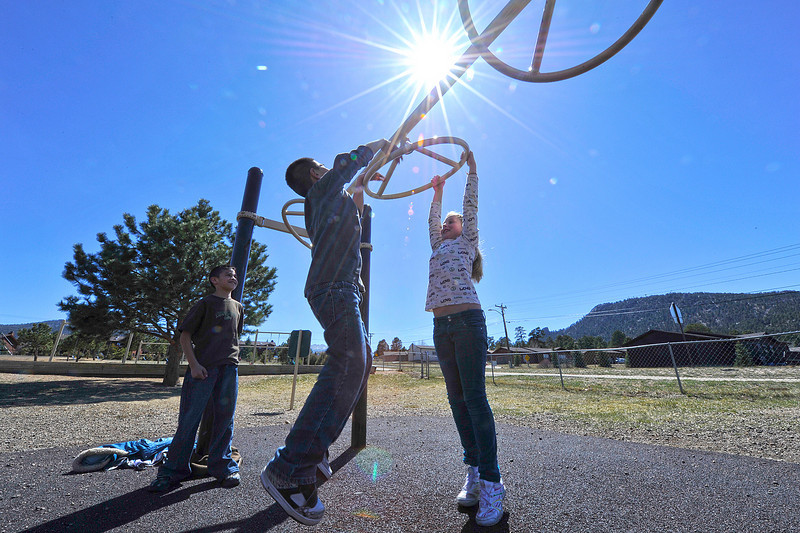Walt Hester | Trail Gazette<br /> Children jump and play on equipment at the Estes Park Elementary Schoolon Monday. The warm, early-spring weather may slip back into cooler temperatures and possibly snow and rain by midweek, but warmer weather should return for the weekend.