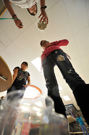 Walt Hester   Trail Gazette<br /> Marleny Avitia, 13, rolls a quarter off of herself into a small, plastic fish bowl at the Estes park Middle School's Scholastic Book Fair Family Night on Thursday. The event had fun games and entertainment as well as the book fair.