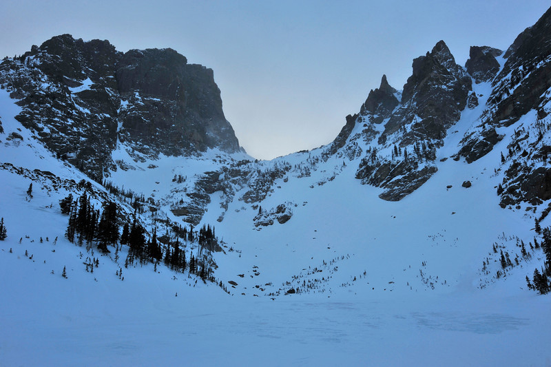 Walt Hester | Trail-Gazette<br /> Hallett Peak and the Dragon's Tail crags of Flattop tower above Emerald Lake. While not quite the highest body of water in the drainage, Emerald Lake is as high as most people are willing to hike any time of year, much less in the cold of winter.