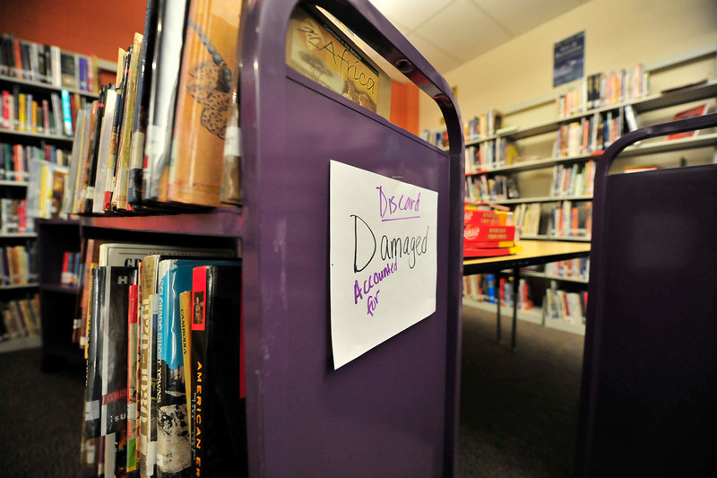 Walt Hester | Trail-Gazette<br /> Carts of damaged books sit idelly by in the Estes Park Middle School library on Wednesday. I sprinkler head in the classroom above the library broke on New Year's night, sending a torrent into the room below and damaging as many as 1,000 books.