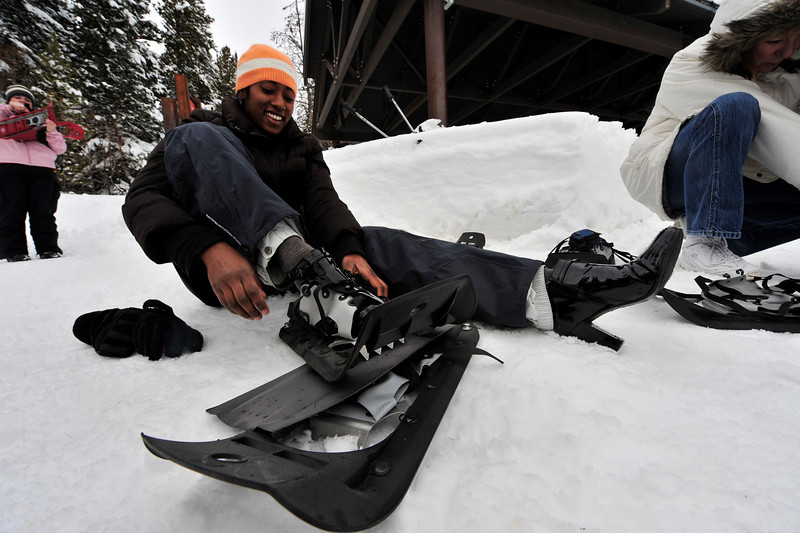 Walt Hester   Trail-Gazett<br /> Anu Godishala of Buffalo, N.Y. swears her high-healed shoes are waterproof as she straps snowshoes to them at Bear Lake on Wednesday.