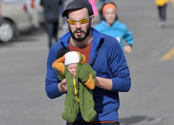 Walt Hester | Trail Gazette<br /> Ryan Fulton of Glenwood Springs helps his 23-day-old daughter, Emberlyn Zytka Zuba Fulton, across the finish line of Sunday's 5K Frost Giant.