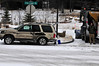 """Walt Hester   Trail Gazette<br /> A plow driver waits at the scene of an apparent weather-related accedent at Fish Creek Road and Brodie Avenue on Monday. The driver of the SUV, Jim Austin, seemed unhurt, though his wife, Jean, said """"We'll wait to see how he feels in the morning."""""""