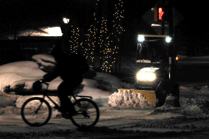 Walt Hester | Trail Gazette<br /> A cyclist pedals past a town bobcat early on Tuesday morning. Town worker were out before 5 a.m. to clear snow from the latest storm.