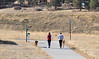 Walt Hester | Trail Gazette<br /> A pair of runners and their four-legged training partners head toward HWY 7 along Carriage Drive on Thursday. Temperatures are expected to stay in the 50s for most of the week in Estes Park.
