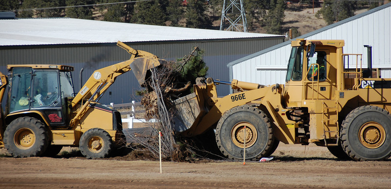 Heavy equipment operators cooperate while removing debris Monday as work on the transportation hub started March 21 at the Fairgrounds at Stanley Park.
