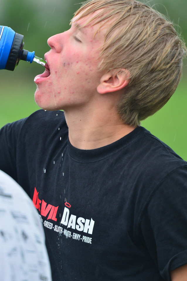 High school soccer player Risto Thompson gets some water for his insides, while rain covers the outside.