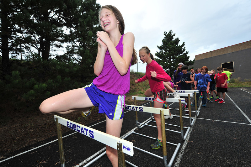 Lucy Baker and her middle school cross country teammates seem to enjoy warming up in Monday's cool rain. Sports teams have had plenty of rain and lightning in the last week, soaking athletes and delaying competition.