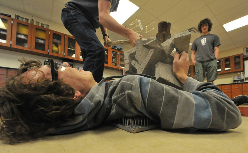 Brian Wenzel, 17, lies on a bed of nails as Alex Franklin smashes a cindar block on top of him. The physics trick remies of the dissipation of energy from the block and the even and wide distribution of weight over the 1,600 nails in the board.