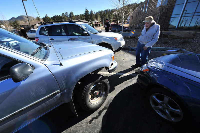 Dr. Bob Krear looks over damage on his truck at the Estes Park Medical Center on Tuesday. There were no serious injuries when an elderly women driving the car on the right hopped the curb in front of her parking space hitting Dr. Krear's car, knocking it into the white car inthe background.