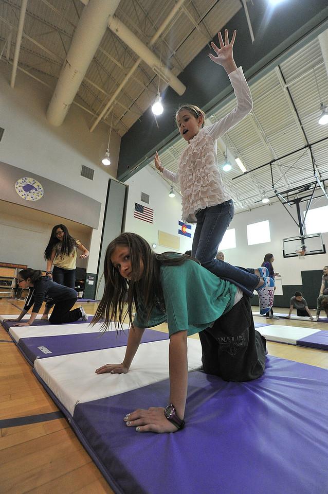 Daffney Harroff, 11, balances atop classmate Jen Johnson during PE at the Estes Park Elementary School on Thursday. The class is focusing on gymnastics and tumbling.