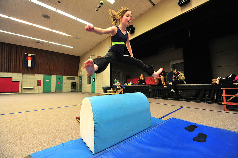Halie Childers, 11, vaults over a soft obstacle during a gymnastics practice in the old elementary school's gym on Monday. Officials are still deciding what to do with the old building.
