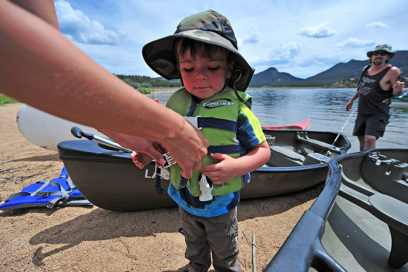 Benjamin Goerich gets a helping hand with his life vest while dad, Justin, of Pinewood Springs, prepares their canoe at the Lake Estes Marine on Thursday. With plenty of warm days still ahead, the Lake Estes Marina is a great place to get some summer fun in.