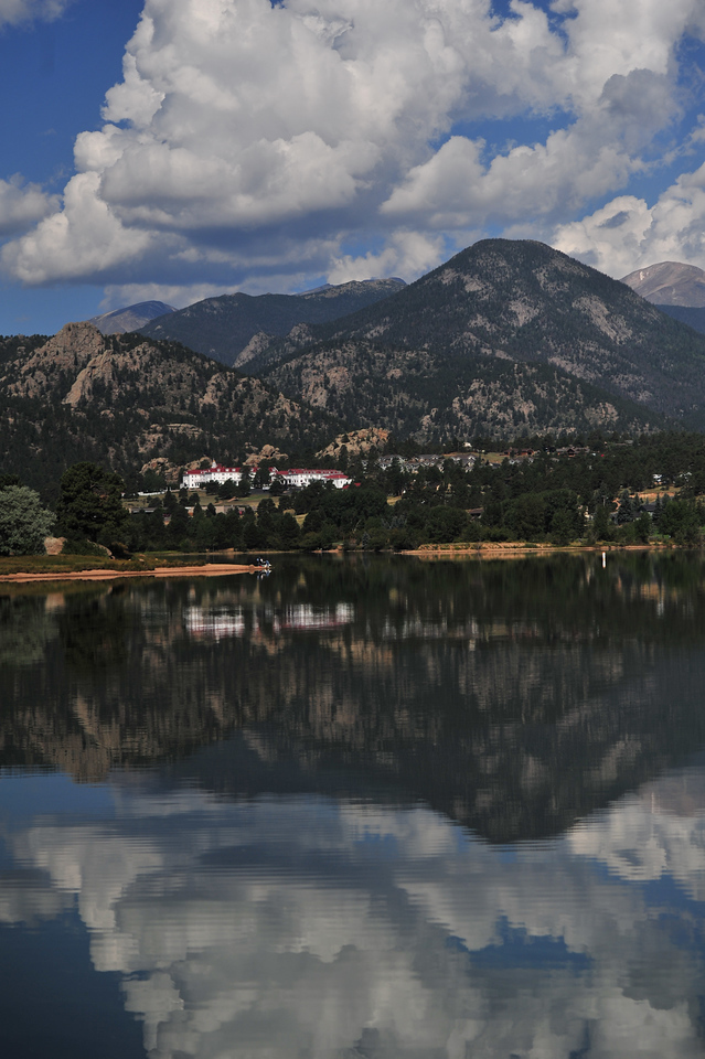 Clouds, mountains, the Stanley Hotel and fisherman reflect off of Lake Estes on Wednesday morning. The hot days of August give recreationists a few more great days to get outdoors.