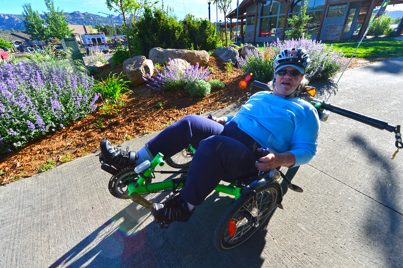 Nina Dixon powers he recumbent bike past the Estes Park Visitor Center on Wednesday. Dixon explained that she suffered from arthritis in her hips and knees and that the bike allowed her to enjoy riding without the pain that a traditional frame would cause.