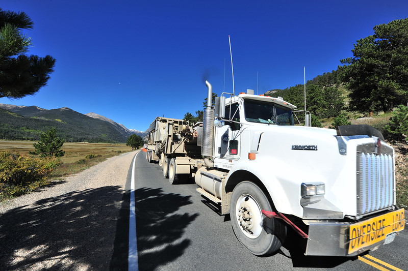 A convoy of heavey road-building equipment makes its way from the west side of Rocky Mountain National Park into Estes Park through Horseshoe Park on Wednesday. The equipment will be used to rebuild Fish Creek among others.