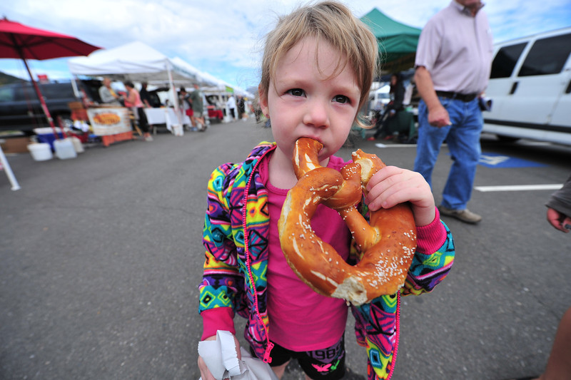 Brynlee Gilliam, 4, of Estes Park enjoys a huge pretzel at the Estes Valley Farmers' Market on Thursday. Just a few weeks remain in the season before the market finishes for another year.