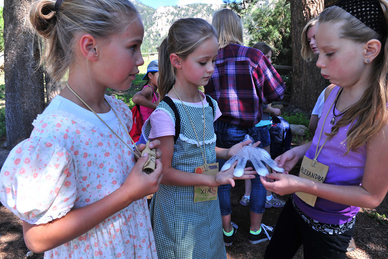 "Julia, 11, and Diana Patrick, 8, of Orange County, California show their ""Garden in a Glove"" to Alexandra Poppin of Estes Park on Tuesday. The group was enjoying the MacGregor Ranch Heritage Camp, a chance to participate while learning area history."