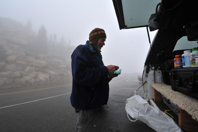 Photographer Greg Balvin of Boulder scoops up breakfast while awaiting the opening of Trail Ridge Road on Wednesday. Heavy fog kept the road closed until after 8:30 on Wednesday.