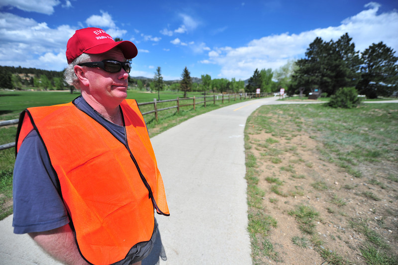Bob Fleischer of the Estes Valley Recreation and Parks district stands along the Lake Estes Trail to warn users of calving elk. A cow elk can be very aggressive and dangerous when protecting a new-born calf.