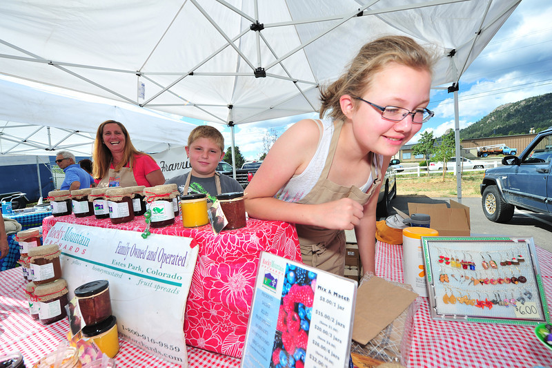 Piper Lasota, 14, of Estes Park shows off jewelry of her own at the Estes Valley Farmers' Market on Thursday. Many local children have jobs for the summer, but few work for themselves.