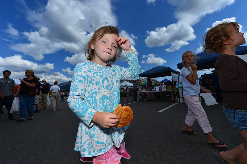 Kylie Gibbs, 4, of Erie enjoys a pastry treat at the Estes Valley Farmers' Market on Thursday. Visitors make the trip even from the Plains to enjoy the market.