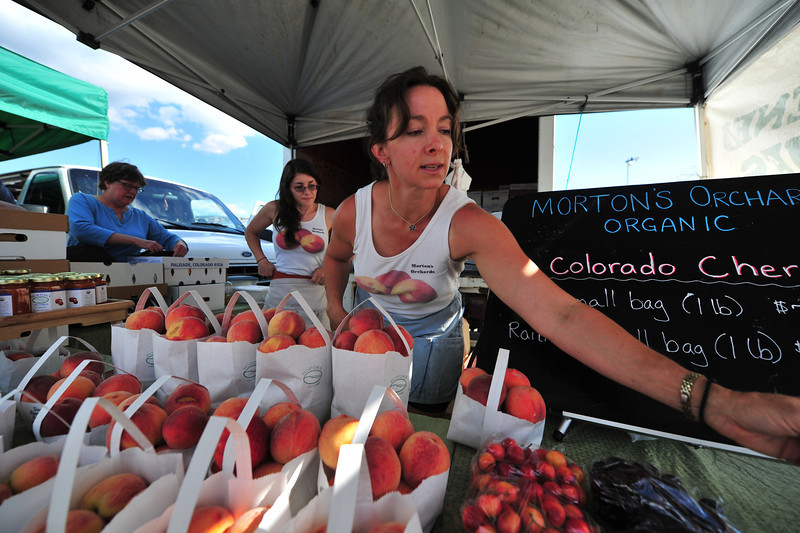 Heather Morton-Burtness reaches for cards at her booth at te Farmers' Market. Her family has grown peaches since 1976.